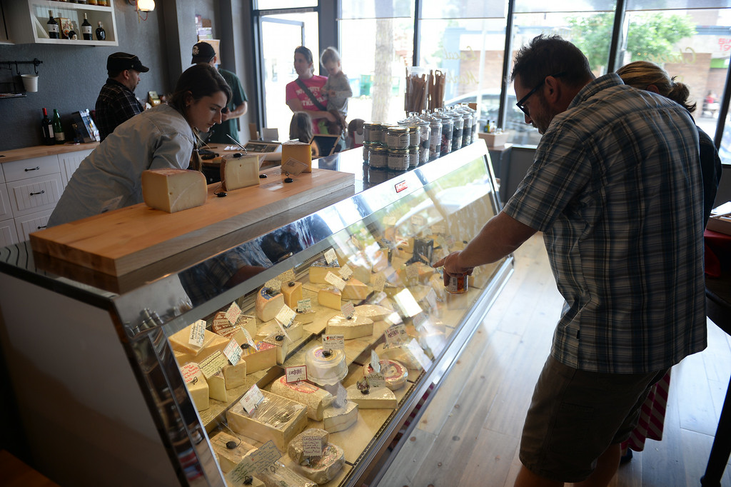 . Olivia Pietrasesa, left, helps a customer  pick out some cheeses at  St. Kilian\'s Cheese Shop and Market in Denver, CO on June 15, 2014.   Jon Marsh and partner Veronica Martinez are the owners of St. Kilians Cheese Shop and Market which specializes in gourmet and international cheeses as well as meats and sausages. (Photo By Helen H. Richardson/ The Denver Post)