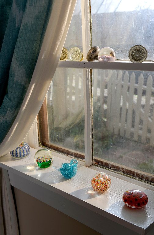 """. Cathy McNamara\'s collection of colorful paper weights and doorknobs at her home on Thursday, July 17, 2014.  Her Georgetown cabin was built in the 1870s and will be on the upcoming Georgetown home tour \""""Brides, Bells and Barons\""""  on July 26th.   (Denver Post Photo by Cyrus McCrimmon)"""