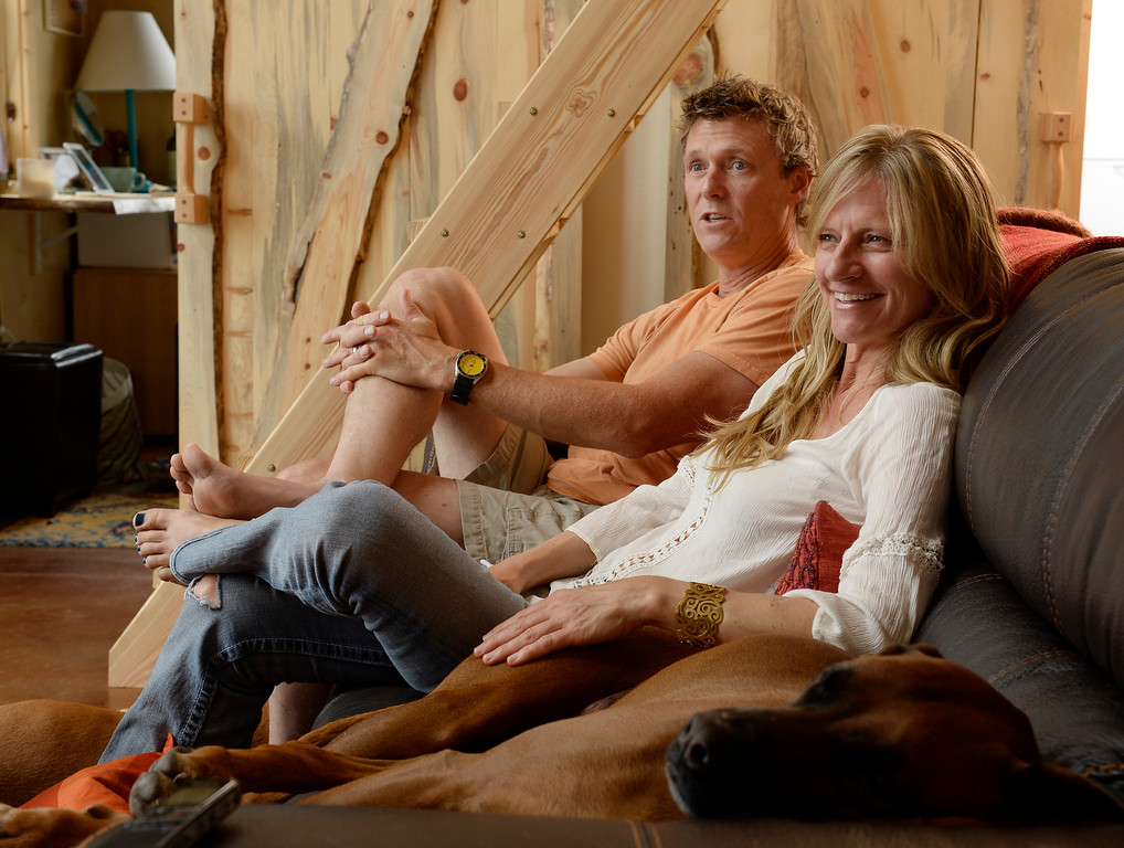 """. David Cottrell and his wife Kristen Moeller in their newly rebuilt home which they rebuilt following the Lower North Fork Fire in 2012. They went from 1200 square feet to 500 square feet. They were at their home which is up Deer Creek Canyon  on Tuesday, July 15, 2014 with one of their 2 dogs, \""""Tigger\"""" who sleeps on the couch. The couple will be featured in an upcoming episode of Tiny House Nation on FYI network. Moeller is author of the new book, \""""What Are You Waiting For? Learn How to Rise to the Occasion Of Your Life.\""""   (Denver Post Photo by Cyrus McCrimmon)"""
