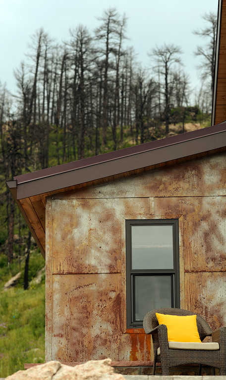 """. David Cottrell and his wife Kristen Moeller have rebuilt their home following the Lower North Fork Fire in 2012. They went from 1200 square feet to 500 square feet. They were at their home which is up Deer Creek Canyon  on Tuesday, July 15, 2014. It has magnificent views but  one can also see five different Colorado forest fire burn zones from past fires from their deck.  The couple will be featured in an upcoming episode of Tiny House Nation on FYI network. Moeller is author of the new book, \""""What Are You Waiting For? Learn How to Rise to the Occasion Of Your Life.\""""  (Denver Post Photo by Cyrus McCrimmon)"""