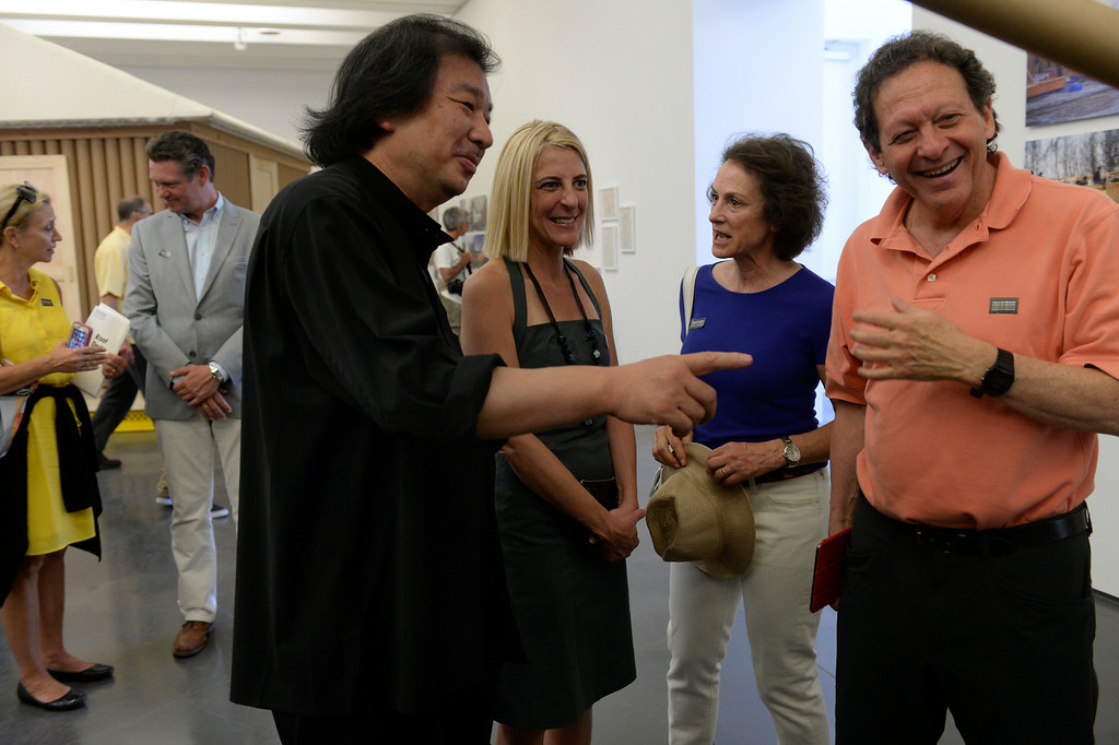 . Japanese architect Shigeru Ban, left, spends time in Gallery 1 with businessman and philanthropist Tom Pritzker, right,  Pritzker\'s wife Margot, second from right, and the director of the museum, Heidi Zuckerman Jacobson. Gallery 1 has Shigeru Ban\'s humanitarian architecture on display. The Aspen Art Museum celebrates its grand opening to the public on Saturday, Aug. 2, 2014. The architect on the project, Shigeru Ban, was there for the celebration which included an official ribbon cutting and fireworks. (Photo by Kathryn Scott Osler/The Denver Post)