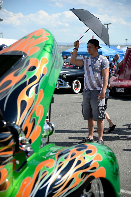 ". A.J. Koon of Denver checks out this 1941 Willys Coupe as more than 13,000 car enthusiasts attend the 10th annual KBPI Rock N Roll car show August 24, 2014 at Bandimere Speedway. There was also a car bash where $1 to take a sledge hammer to a car benefiting ""US Warriors Outside\"" providing wooded veterans the opportunity to enjoy their passion for the outdoors. (Photo by John Leyba/The Denver Post)"