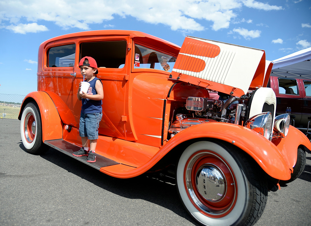". Jesiah Martinez 3 years old of Denver takes a sip of his drink as he gets his picture taken with a 1928 Model A  Tudor. More than 13,000 car enthusiasts attend the 10th annual KBPI Rock N Roll car show August 24, 2014 at Bandimere Speedway. There was also a car bash where $1 to take a sledge hammer to a car benefiting ""US Warriors Outside\"" providing wooded veterans the opportunity to enjoy their passion for the outdoors. (Photo by John Leyba/The Denver Post)"