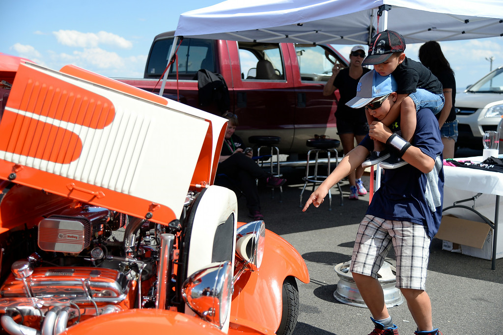 ". Trevor Moonin 12, carries his cousin Cameron Cruz 3 years old as they check out the 1928 Model A Tudor. More than 13,000 car enthusiasts attend the 10th annual KBPI Rock N Roll car show August 24, 2014 at Bandimere Speedway. There was also a car bash where $1 to take a sledge hammer to a car benefiting ""US Warriors Outside\"" providing wooded veterans the opportunity to enjoy their passion for the outdoors. (Photo by John Leyba/The Denver Post)"