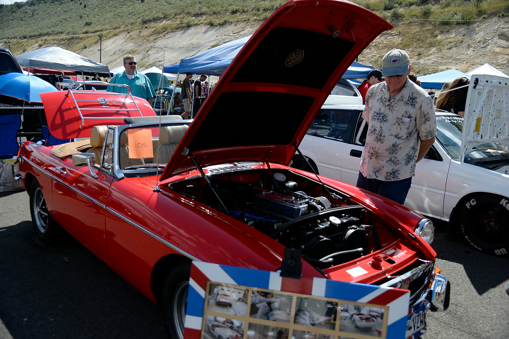 ". Keith Duncan of Thornton checks out this MG as more than 13,000 car enthusiasts attend the 10th annual KBPI Rock N Roll car show August 24, 2014 at Bandimere Speedway. There was also a car bash where $1 to take a sledge hammer to a car benefiting ""US Warriors Outside\"" providing wooded veterans the opportunity to enjoy their passion for the outdoors. (Photo by John Leyba/The Denver Post)"