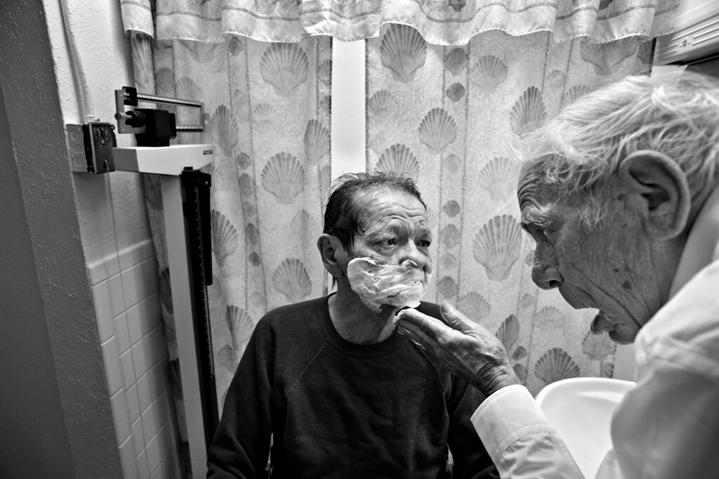 """. Cecil Bethea shaves the face of his partner, Carl Shepherd, during one of Cecil\'s many visits to The Spearly Center, where Carl lives, in Denver, Colo. Cecil bathes and shaves Carl\'s face every other day. \""""As I remember in the old time wedding vows, there was a phrase in there, \'in sickness and in health,\'\"""" Cecil says. \""""Well this is certainly sickness. And if I didn\'t do it, who would... I\'m the only one he has.\"""" (Photo By Craig F. Walker/The Denver Post)"""