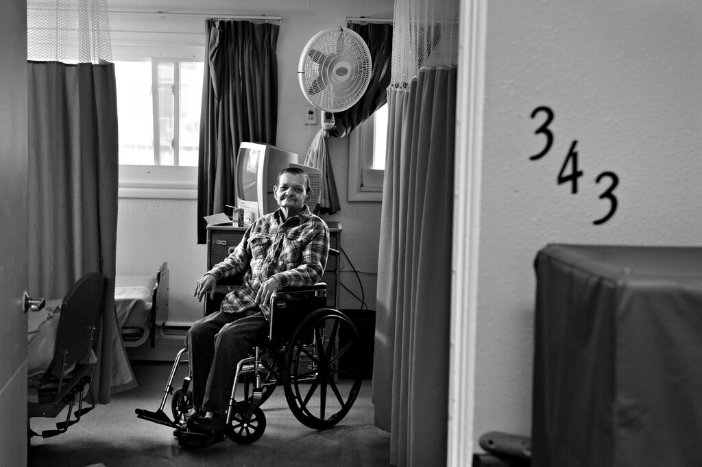 """. Carl watches from his room as his partner, Cecil, leaves the The Spearly Center. Cecil said it was incredibly difficult to leave when Carl was first admitted to the nursing home. \""""That was terrible... when I would leave he would want to go home with me, and we would have to get the attendants to hold him,\"""" Cecil said. \""""That was hard, mighty hard.\"""" (Photo By Craig F. Walker/The Denver Post)"""