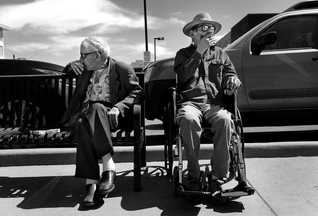 """. Conversation is scarce as Cecil and Carl smoke cigarettes near The Spearly Center before Carl returns him to his room. Carl, who was admitted to the nursing home over a year ago, suffers from dementia. \""""You see, he\'s not Carl anymore,\"""" Cecil said. \""""He\'s almost like a little child. When I walk in to see him, the first thing he asks me is \'Can we go for a smoke?\'\"""" Cecil said he sometimes feels like Carl\'s cigarette dispenser, which bothers him. \""""I chatter like an irritated squirrel, and he just sits there. That\'s mighty hard to take.\"""" (Photo By Craig F. Walker/The Denver Post)"""