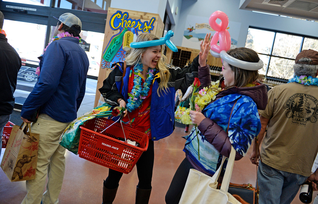 . Mary Kate Douglas, left, gives her friend, Paige Mullen, a high five as they wait in line to checkout during the grand opening of specialty grocer Trader Joe\'s located on Colorado Blvd. and East 8th Avenue in Denver, February, 14 2014. Two other Trader Joe\'s locations in Colorado will also open today. (Photo by RJ Sangosti/The Denver Post)