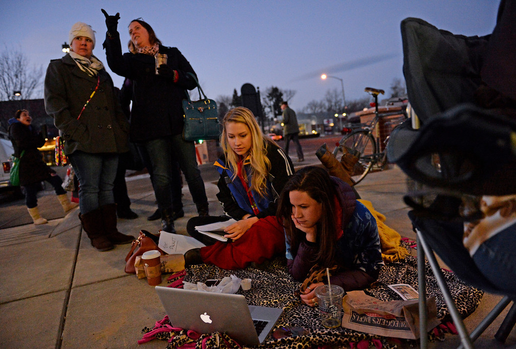 . DENVER, CO - FEBRUARY 14: Mary Kate Douglas, left, and Paige Mullen watch a movie as they wait in line for the grand opening of specialty grocer Trader Joe\'s located on Colorado Blvd. and East 8th Avenue in Denver, February, 14 2014. Two other Trader Joe\'s locations in Colorado will also open today. (Photo by RJ Sangosti/The Denver Post)