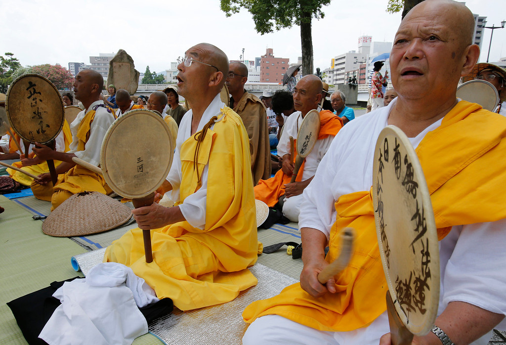 . Buddhist monks chant a Buddhist mantra while beating drums in front of the Atomic Bomb Dome in Hiroshima, western Japan, Monday, Aug. 5, 2013. (AP Photo/Shizuo Kambayashi)