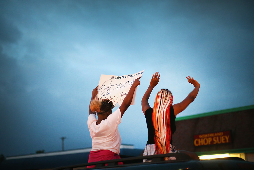. Demonstrators raise their arms during a protest against the killing of teenager Michael Brown on August 17, 2014 in Ferguson, Missouri.  Despite the Brown family\'s continued call for peaceful demonstrations, violent protests have erupted nearly every night in Ferguson since his death. (Photo by Scott Olson/Getty Images)
