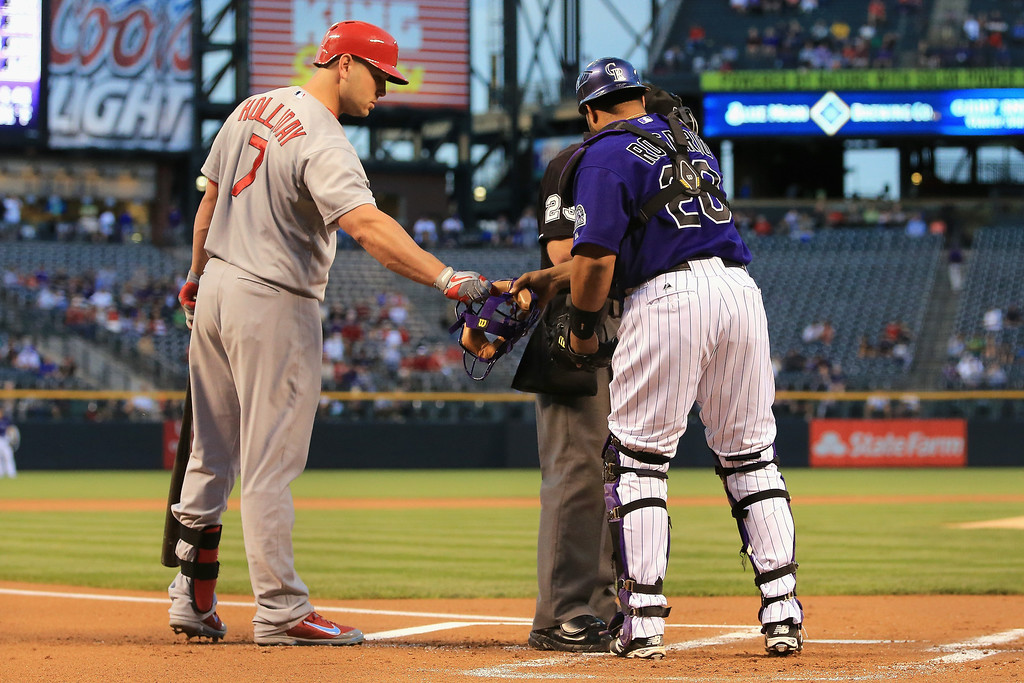 . Matt Holliday #7 of the St. Louis Cardinals hands catcher Wilin Rosario #20 of the Colorado Rockies his mask during the first inning at Coors Field on September 17, 2013 in Denver, Colorado.  (Photo by Doug Pensinger/Getty Images)