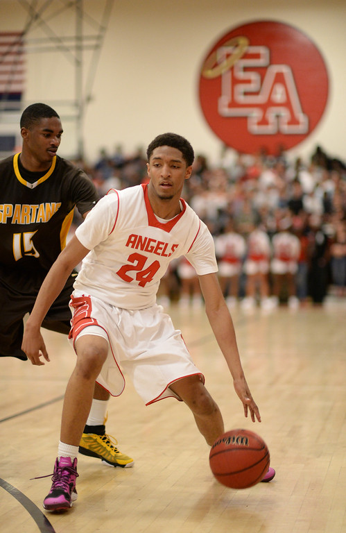 . DENVER, CO. JANUARY 24: Dominique Collier of East High School (24) controls the ball against Treyvon Andres of Thomas Jefferson High School during the 2nd half of the game at East High School in Denver, Colorado January 24, 2014. East High School won 91-62. (Photo by Hyoung Chang/The Denver Post)