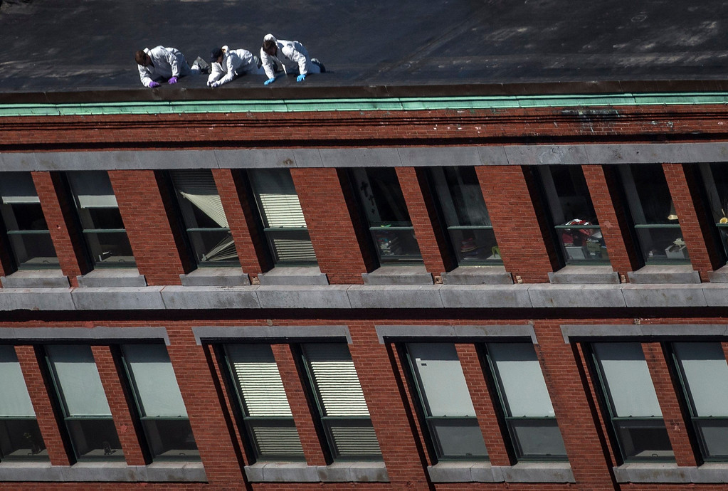 . Investigators lean over the rooftop of a building located above the site of a bomb blast on Boylston Street two-days after multiple explosions at the Boston Marathon killed three and injured 176 in Boston, Massachusetts April 17, 2013. Investigators believe they have identified a suspect in the Boston marathon bombing from security video, a U.S. law enforcement source said.  REUTERS/Adrees Latif