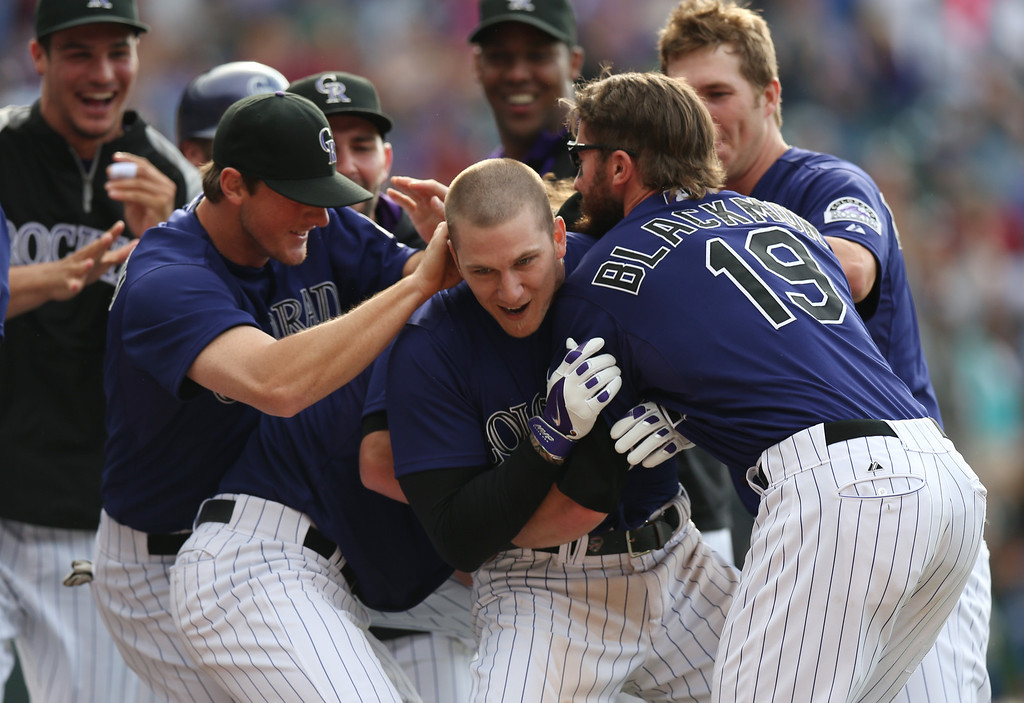 . Colorado Rockies\' Brandon Barnes, center, celebrates driving in the winning run with teammates Rex Brothers, left, and Charlie Blackmon against the Los Angeles Dodgers in the 10th inning of the Rockies\' 5-4 victory in 10 innings in a baseball game in Denver on Saturday, June 7, 2014. (AP Photo/David Zalubowski)