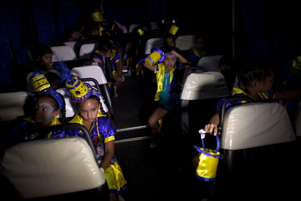 ". Member of the murga ""Los amantes de La Boca\"" wait inside a bus before heading to carnival celebrations in Buenos Aires, Argentina, Saturday, Feb. 2, 2013. Members of the murga \""Los amantes de La Boca\"" rehearse before participating in carnival celebrations in Buenos Aires, Argentina, Saturday, Feb. 2, 2013. Argentinians\' carnival celebrations may not be as well-known as the ones in neighboring Uruguay and Brazil, but residents of the nation\'s capital are equally passionate about their \'murgas,\' or traditional musical troupes. The murga \""Los amantes de La Boca\"" or \""The Lovers of The Boca\"" is among the largest, with about 400 members. It\'s a reference to the hometown Boca Juniors, among the most popular soccer teams in Argentina and the world. (AP Photo/Natacha Pisarenko)"