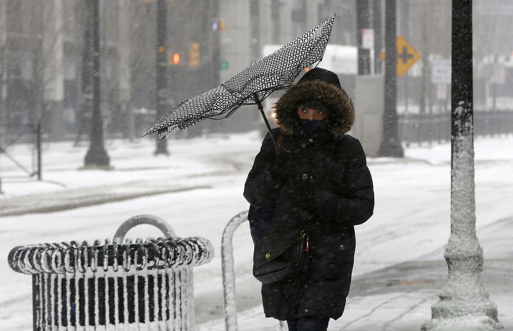 . Wind flips over the canopy of an umbrella as a woman walks in gusty wind during a winter storm, Tuesday, Jan. 21, 2014, in Jersey City, N.J.  (AP Photo/Julio Cortez)