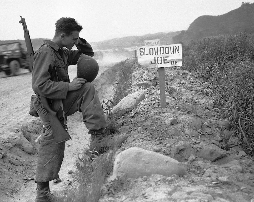 . Pvt. Dudley Lufkin, Hollywood, Calif. looks over a series of \'Burma Shave\' type signs along a road in the First Cavalry Division area of the Korean front on July 9, 1951. They say, in series: \'Slow down, Joe.\' (AP Photo)