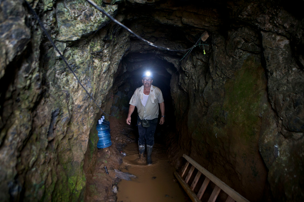 . A miner walks inside the El Comal mine during rescue operations at the gold and silver mine after a landslide trapped at least 24 miners inside, in Bonanza, Nicaragua, Friday, Aug. 29, 2014. Rescuers on Friday located 20 of at least 24 gold miners trapped by a landslide in northern Nicaragua, but were not immediately able to bring them to safety. (AP Photo/Esteban Felix)