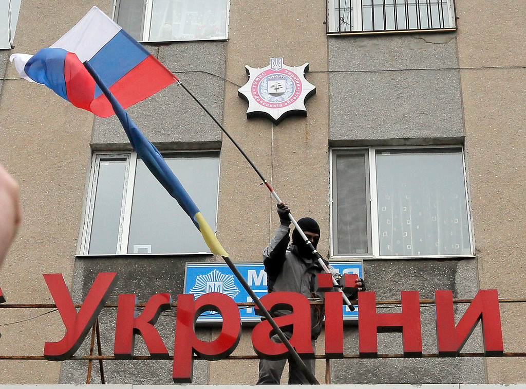 ". A pro-Russian man places a Russian flag over a police station during its mass storming in the eastern Ukrainian town of Horlivka on Monday, April 14, 2014.  The text reads: Ukrainian police station in Horlivka"". Several government buildings has fallen to mobs of Moscow loyalists in recent days as unrest spreads across the east of the country.  (AP Photo/Efrem Lukatsky)"
