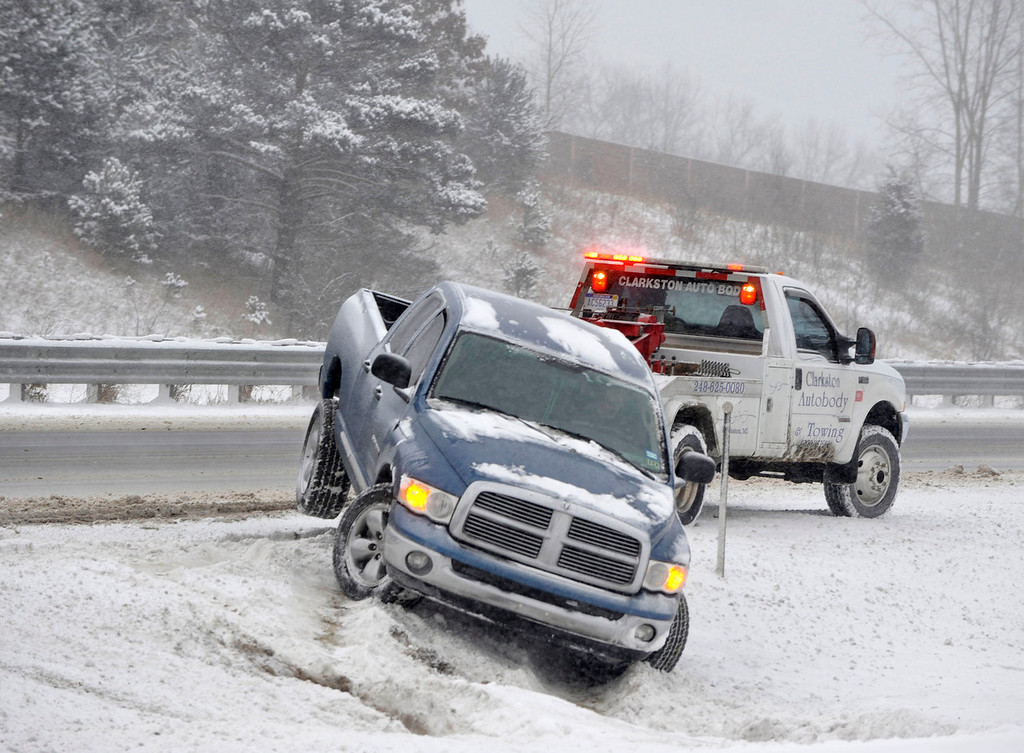 . A pickup trucked is pulled out of the snow along southbound  I-75 near  Dixie Highway by a tow truck in Clarkston, Mich., Thursday, Jan. 2, 2014. Roads were slippery and snow-covered in Detroit and its suburbs for the Thursday morning commute.  (AP Photo/Detroit News,  Charles V. Tines)