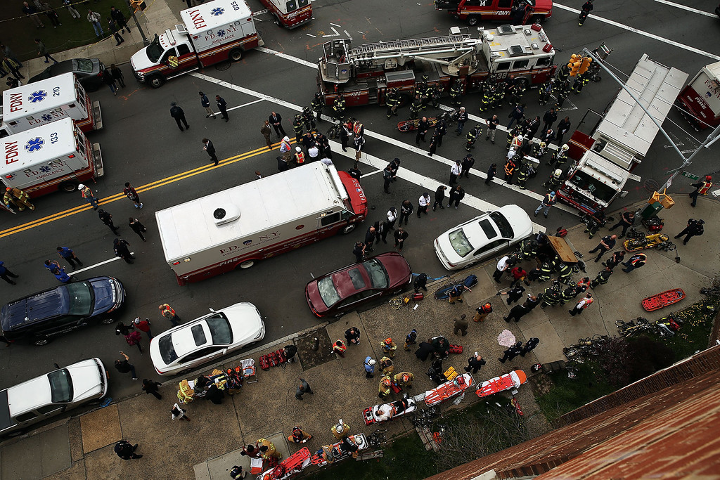 . New York City firefighters  and rescue workers use an emergency staircase to evacuate passengers from a derailed F train on May 2, 2014 in the Woodside neighborhood of the Queens borough of New York City. According to the Metropolitan Transportation Authority  (MTA) the express F train was bound for Manhattan and Brooklyn when it derailed at 10:40 a.m. about 1,200 feet from the 65th station in Woodside, Queens with hundreds of passengers on board.  (Photo by Spencer Platt/Getty Images)