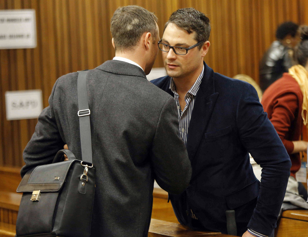 . South African Paralympic athlete Oscar Pistorius (L), accused of murdering his girlfriend Reeva Steenkamp, talks to his brother Carl Pistorious (R) on the second day of his trial at the North Gauteng High Court in Pretoria, on March 4, 2014. Lawyers for Paralympian Oscar Pistorius will on March 4 resume a searing cross-examination of a key witness at his murder trial who claims to have heard screams, then shots, as his girlfriend was killed. The second day of Pistorius\'s trial for the Valentine\'s Day killing of Reeva Steenkamp will begin with lawyer Barry Roux redoubling efforts to pick apart the prosecution\'s premier witness.  (Antoine de RasAntoine de Ras/AFP/Getty Images)