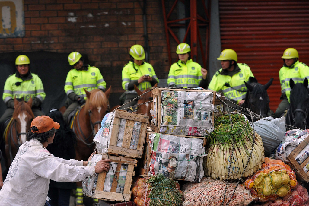 . A worker secures a load of food while a group of policemen on horseback stand guard at the main food market in Bogota, on August 24, 2013 as a strike of farmers demanding government subsidies and greater access to land continues. A six-day-old farmworkers\' protest in Colombia is creating shortages and rising prices of ceirtain food products in Bogota. Since the protests began Monday, farmworkers have closed roads at dozens of points in across the country, blocking the passage of cargo trucks and other vehicles from makeshift camps erected on sides of roads. GUILLERMO LEGARIA/AFP/Getty Images