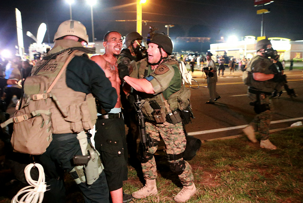 . A protestor is detained Monday, Aug. 18, 2014, in Ferguson, Mo. The Aug. 9 shooting of Michael Brown by police has touched off rancorous protests in Ferguson, a St. Louis suburb where police have used riot gear and tear gas. (AP Photo/St. Louis Post-Dispatch, Christian Gooden)