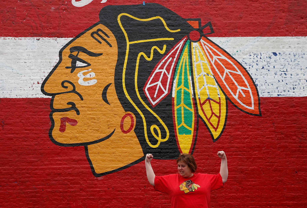 . Chicago Blackhawks fan Susan Bieszczat jokes around in front of a mural of the team\'s logo painted on the side of a building before the NHL Stanley Cup hockey finals in Chicago, Illinois June 12, 2013. The Blackhawks will face the Boston Bruins in the finals. REUTERS/Jim Young