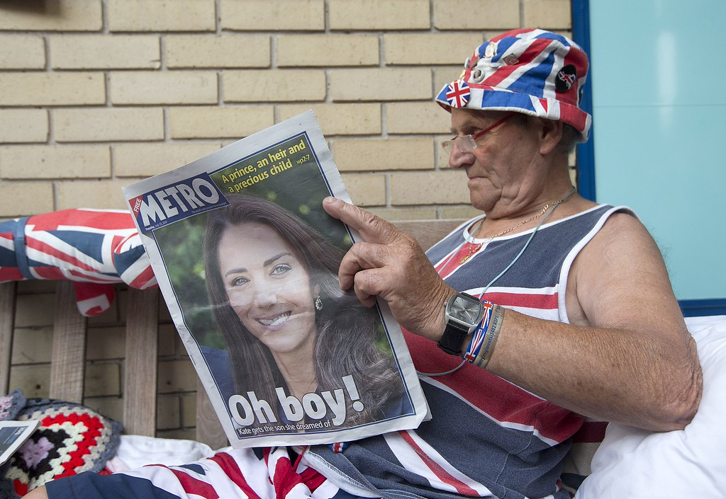 . Royal Supporter Terry Hutt reads a newspaper announcing the birth of the newest member of Britain\'s royal family outside St Mary\'s Hospital in London, on July 23, 2013. Britain\'s new baby prince follows his father and late grandmother by being born under the zodiac sign of Cancer, suggesting he will be a strong leader, according to astrologists.  AFP PHOTO / JUSTIN TALLIS/AFP/Getty Images