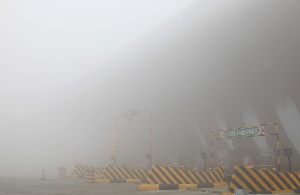 . A toll booth is shut down as heavy smog spreads on a highway as vehicles are forced to wait due to heavy smog in Jilin, northeast China\'s Jilin province on October 22, 2013.     AFP PHOTOSTR/AFP/Getty Images