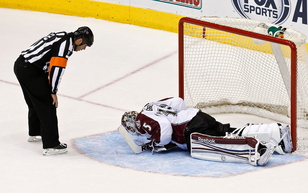 . An injured Colorado Avalanche\'s Jean-Sebastien Giguere stays on the ice as referee Justin St. Pierre talks with the goalie during the third period in an NHL hockey game against the Phoenix Coyotes, on Friday, April 26, 2013, in Glendale, Ariz.  The Avalanche defeated the Coyotes 5-4 in a shootout. (AP Photo/Ross D. Franklin)