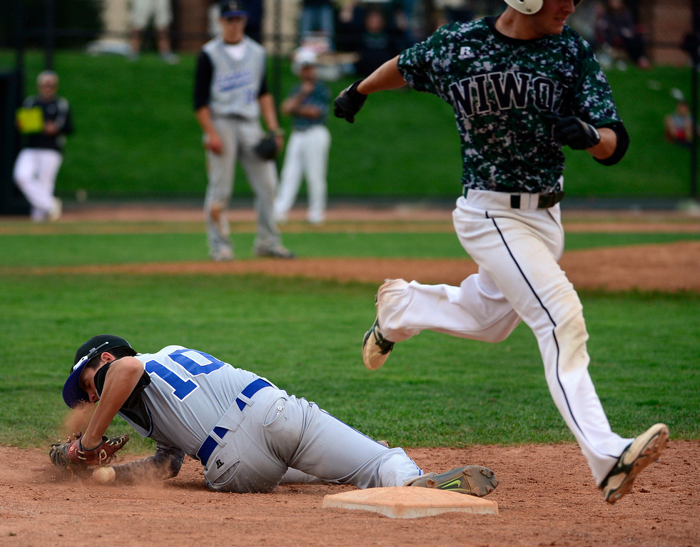 . LAKEWOOD, CO - MAY 23: Niwot\'s Kai Halsey is safe at first base as Longmont\'s Brett Sterkel drops the ball. The Longmont Trojans take on the Niwot Cougars in the 4A Baseball State Semi-Final Championships. (Kathryn Scott Osler, The Denver Post)