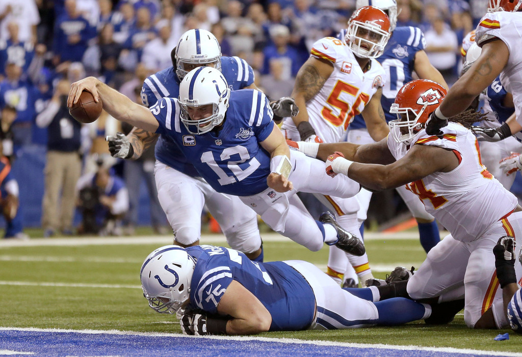 . Indianapolis Colts quarterback Andrew Luck (12) dives for a touchdown after recovering a fumble by the Colts\' Eric Berry during the second half of an NFL wild-card playoff football game against the Kansas City Chiefs Saturday, Jan. 4, 2014, in Indianapolis. (AP Photo/Michael Conroy)