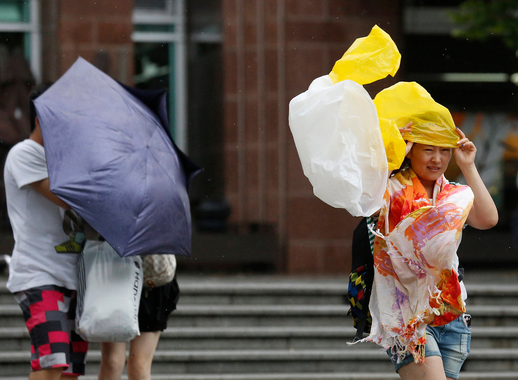 . A woman braves strong wind at the Victoria Peak in Hong Kong Tuesday, Aug. 13, 2013. The Observatory said Typhoon Utor intensified slightly as it moves towards the western coast of Guangdong. The typhoon battered the northern Philippines on Monday, toppling power lines and dumping heavy rain across cities and food-growing plains. (AP Photo/Kin Cheung)