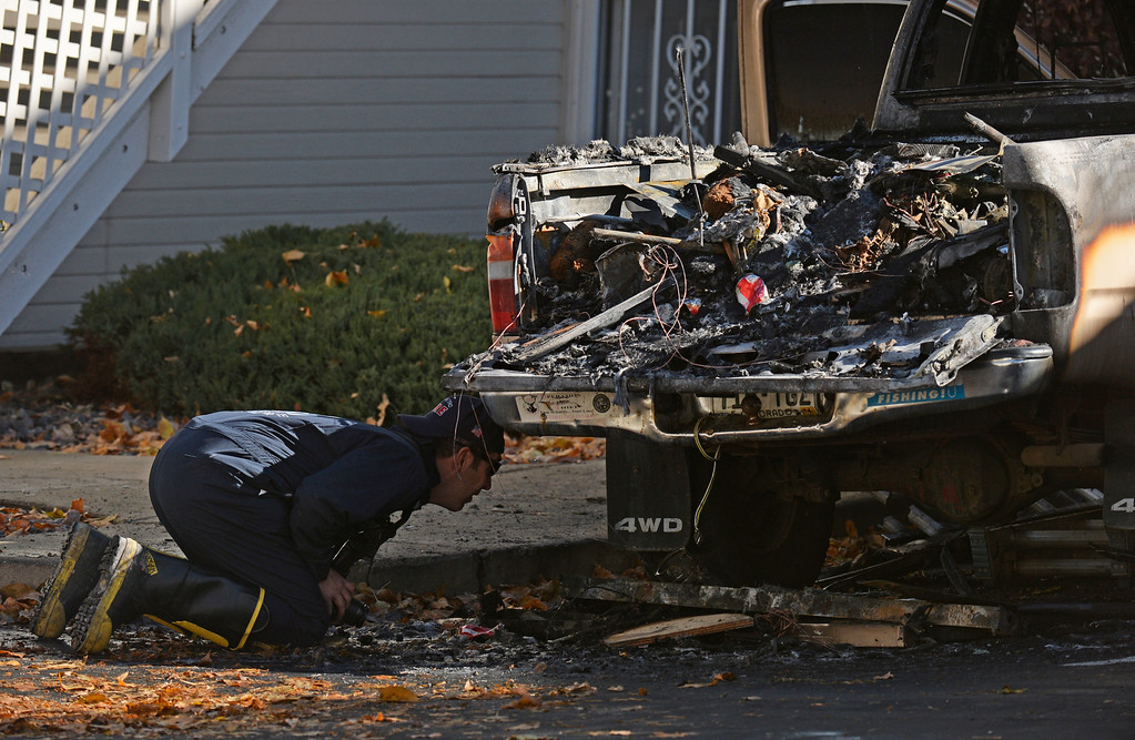 ". A West Metro Fire Investigator looks over a fire that was set in a truck outside an apartment complex, October 22, 2013. Firefighters responded to four separate fires in Lakewood early Tuesday morning that they are calling ""suspicious.\"" (Photo By RJ Sangosti/The Denver Post)"