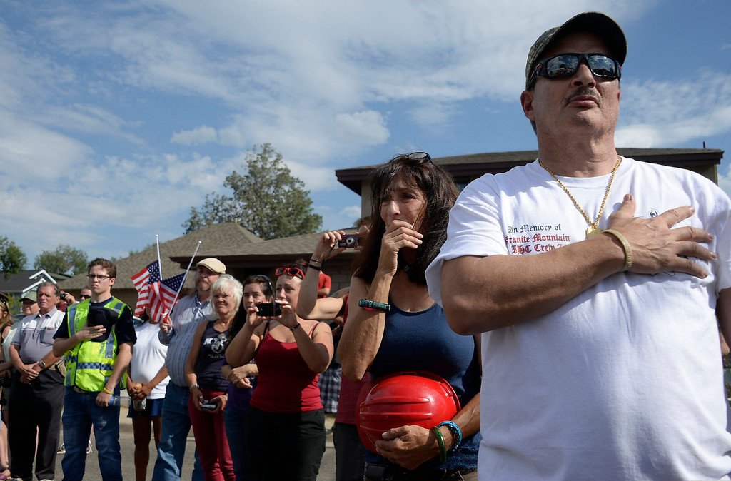 . Prescott residents stand up as the procession of hearses carrying the remains of the 19 members of the Granite Mountain Hotshots firefighting team, who were killed fighting the Yarnell Fire, pass by their fire station in Prescott, Arizona July 7, 2013. A solemn procession of 19 white hearses carrying the remains of firefighters killed battling an Arizona wildfire left Phoenix accompanied by police motorcycle outriders on Sunday on a final journey passing through the crew\'s hometown. REUTERS/Gene Blevins