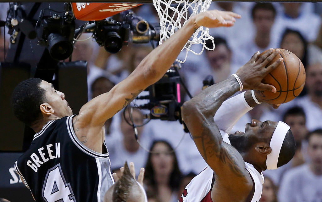 . Miami Heat\'s LeBron James (R) shoots while being guarded by San Antonio Spurs\' Danny Green during the second quarter in Game 7 of their NBA Finals basketball playoff in Miami, Florida June 20, 2013. REUTERS/Mike Segar