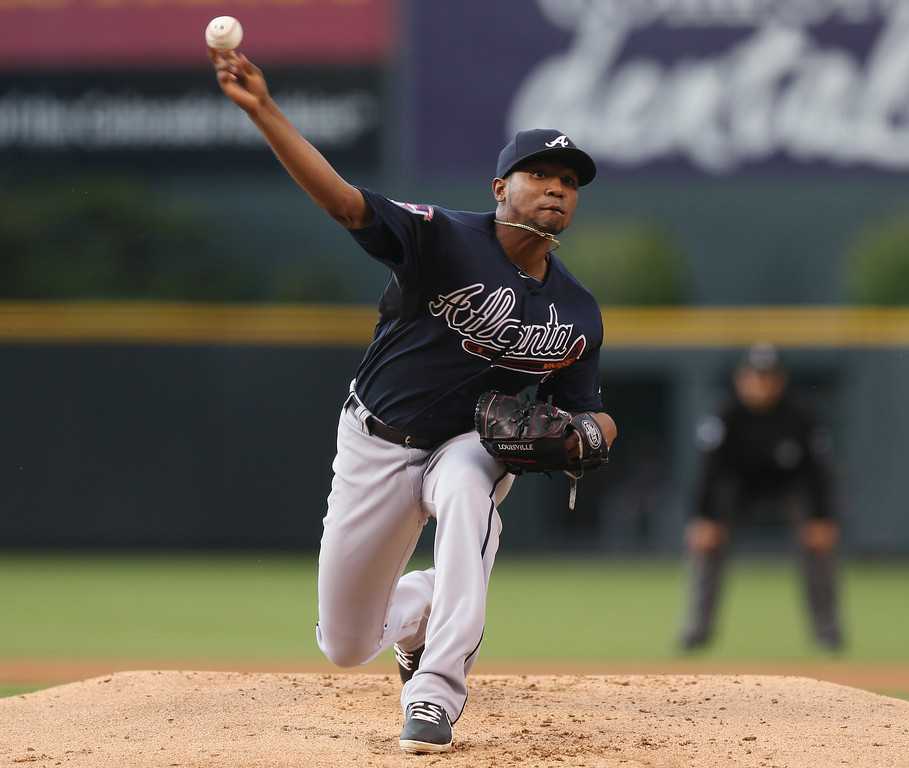 . Atlanta Braves starting pitcher Julio Teheran works against the Colorado Rockies in the first inning of a baseball game in Denver on Wednesday, June 11, 2014. (AP Photo/David Zalubowski)