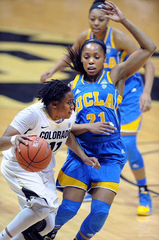 . Colorado\'s Brittany Wilson drives past UCLA\'s Nirra Fields during the second half of an NCAA college basketball game Friday, Feb. 28, 2014, in Boulder, Colo. Colorado won 62-42. (AP Photo/Daily Camera, Cliff Grassmick)