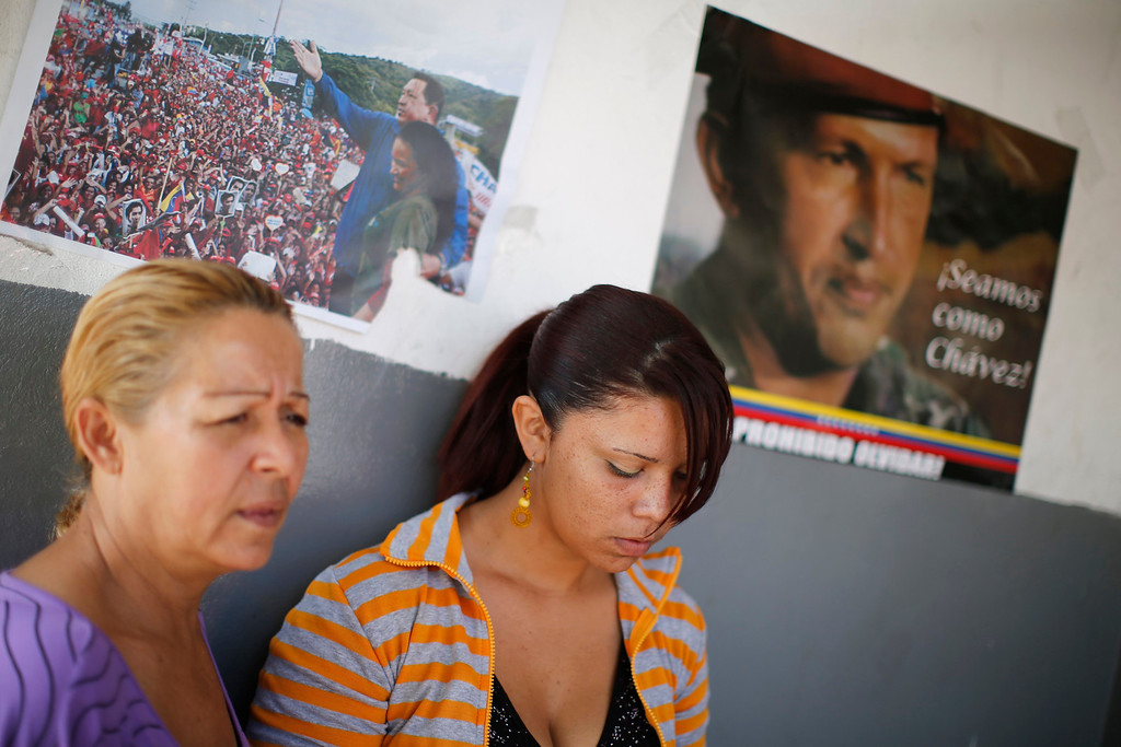 """. Women stand next to a poster of Venezuelan President Hugo Chavez outside the Caracas military hospital in Caracas March 5, 2013. Chavez\'s adoring supporters prayed and wept on Tuesday over a serious setback in his battle against a cancer that threatens to end his 14-year rule of the South American OPEC member. In one of the gloomiest announcements to date on Chavez\'s health, the government said on Monday night that his breathing problems had worsened and he was suffering from a \""""severe\"""" new respiratory infection in a Caracas military hospital. REUTERS/Jorge Silva"""