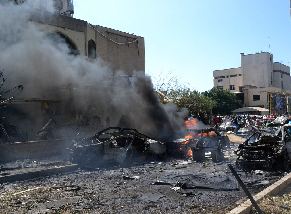 . Burned and destroyed cars are seen at the entrance of a mosque, left, which was attacked by a car bomb, in the northern city of Tripoli, Lebanon, Friday Aug. 23, 2013.  (AP Photo)