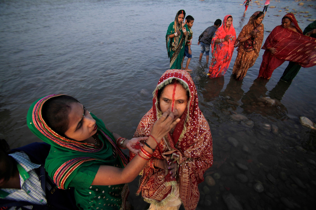 . A Hindu woman puts vermillion powder on the forehead of another during prayers at sunset in the Tawi River to mark Chhath Puja festival in Jammu, India, Friday, Nov. 8, 2013.  (AP Photo/Channi Anand)