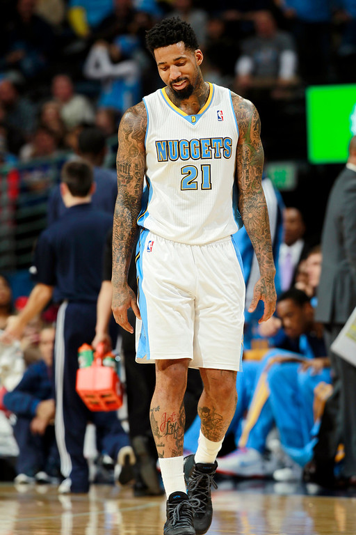 . Denver Nuggets forward Wilson Chandler walks on the court as the Nuggets fall behind the Philadelphia 76ers in the third quarter of the Sixers\' 114-102 victory in an NBA basketball game in Denver on Wednesday, Jan. 1, 2014. (AP Photo/David Zalubowski)