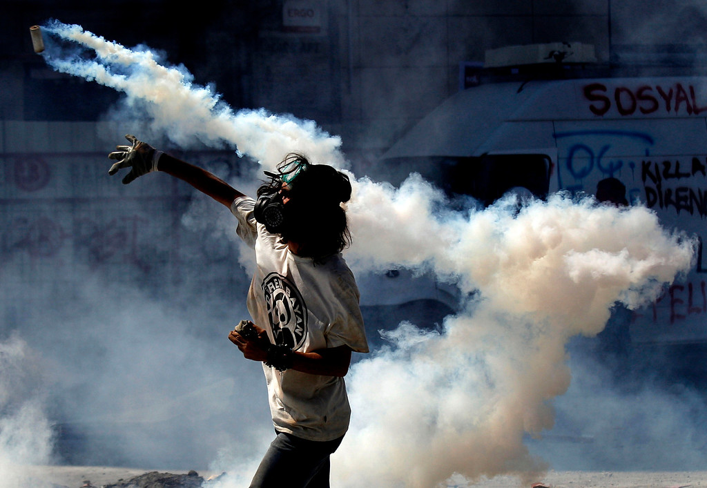 . A protester throws back to police a tear gas canister during clashes in Taksim square in Istanbul, Tuesday, June 11, 2013.  (AP Photo/Kostas Tsironis)