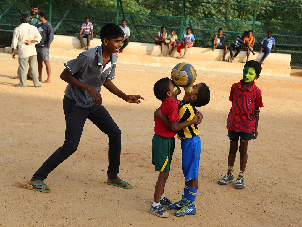 . Indian children with faces painted in colors resembling those of the Brazil\'s flag place the ball on their faces as others watch, during a game of soccer in Bangalore, India, Tuesday, June 10, 2014. Soccer fans around the world are gearing up to watch the World Cup soccer tournament that kicks off Thursday in Brazil. (AP Photo/ Aijaz Rahi)