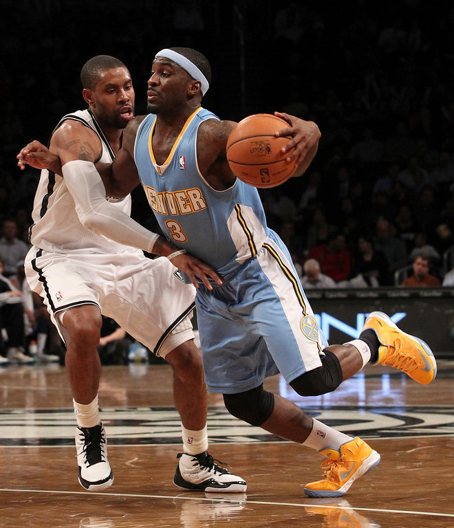 . Brooklyn Nets\' C.J. Watson, left, fouls Denver Nuggets\' Ty Lawson during the second half of an NBA basketball game on Wednesday, Feb. 13, 2013, at Barclays Center in New York. The Nuggets won 119-108. (AP Photo/Mary Altaffer)