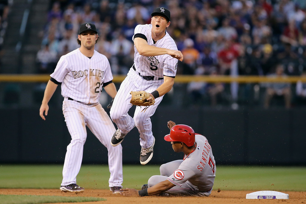 . DENVER, CO - AUGUST 15:  Second baseman DJ LeMahieu #9 of the Colorado Rockies gets a force out on Ramon Santiago #7 of the Cincinnati Reds but is unable to turn the double play on Johnny Cueto #47 of the Cincinnati Reds in the fourth inning at Coors Field on August 15, 2014 in Denver, Colorado.  (Photo by Doug Pensinger/Getty Images)